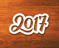 Happy New Year 2017 vector greeting card. New Year 2017 paper label with calligraphic number on wood background. Vector greeting card design template for winter Stock Photography