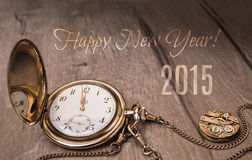 Happy New Year 2015! Vintage watch showing five to twelve. Happy New Year 2015! Vintage watch on a wooden background showing five to twelve royalty free stock photography