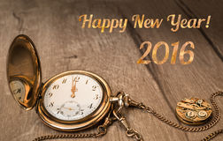 Happy New Year 2016! Vintage watch showing five to twelve. Vintage watch on a wooden background showing five to twelve and caption Happy Year 2016 stock photo