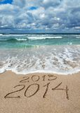 Happy New Year 2014 wash away 2013 concept on sea beach. Happy New Year 2014 wash away year 2013 concept on sea sand beach Royalty Free Stock Images