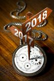 Happy New Year 2018 - Watch with Signs. Happy New Year 2018 - Old pocket watch with two wooden signs with arrows and the years 2017 and 2018 Royalty Free Stock Photography