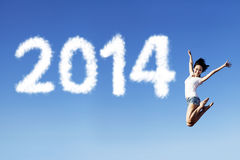 Happy new year 2014. Happy woman jumping on the air with cloud design of new year 2014 Royalty Free Stock Photos