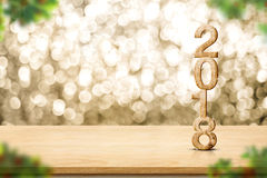 Happy new year 2018 on wood table and blur Christmas tree foregr. Ound at blur sparkling gold bokeh light wall,panoramic banner for display or montage of product Royalty Free Stock Photos