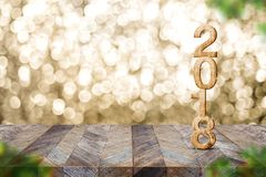 Happy new year 2018 on wood table and blur Christmas tree foreground at blur sparkling gold bokeh light wall,panoramic banner for stock photo