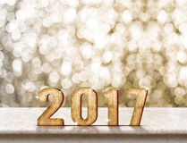Happy New Year 2017 wood texture on marble table with sparkling. Gold bokeh wall,Holiday concept