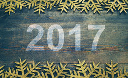 Happy New Year 2017 on a wooden background. Number 2017 on vintage style. Wooden texture background. Snowflakes on a wooden board