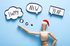 Happy New Year. Wooden puppet doll over blue background stock image