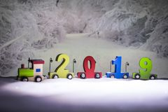 2019 happy new year,wooden toy train carrying numbers and Cristmas tree,covering snow royalty free stock photography