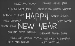 Happy new year word cloud. Happy new year in many different languages written on a chalkboard Stock Photos