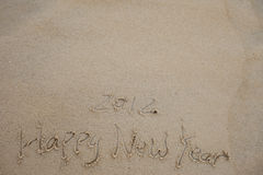 Happy new year word  in the sand beach Stock Photos