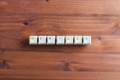 Happy new year word on computer keyboard keys buttons on wooden. Happy new year word written using white computer keyboard keys buttons on wooden background Royalty Free Stock Photos