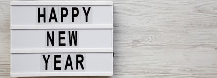 `Happy new year` words on modern board over white wooden background, top view. Overhead, flat lay, from above. Copy space stock image