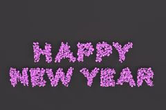 Happy New Year words from violet balls on black background. New Year sign. 3D rendering illustration Stock Photos