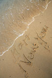 Happy new year write on beach Stock Photo