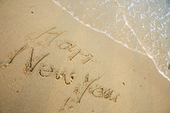 Happy new year write on beach Stock Image
