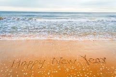 Happy new year write on beach stock photo