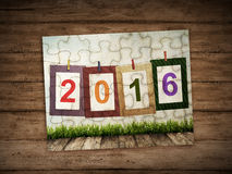 Happy new year writing in puzzle. 2016 number in puzzle with wooden background Stock Image