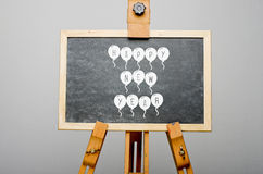 Happy New Year written on balloons on black chalkboard, easel painting Stock Photo