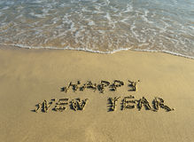 Happy new year written in beach Stock Photos