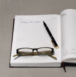 Happy new year written on a diary page Royalty Free Stock Photos