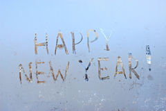 Happy new year written on frosty winter window background Stock Photography