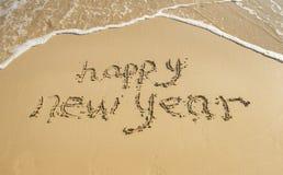 Happy new year written in sand Stock Photo