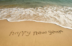 Happy new year written in sand Royalty Free Stock Image