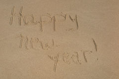 Happy new year written in the sand Royalty Free Stock Images