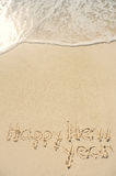 Happy New Year Written in Sand on Beach Royalty Free Stock Photo