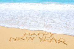Happy New Year on the beach. Happy New Year written on sand of an exotic beach Stock Image