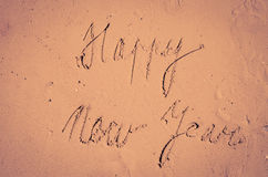 Happy New Year written into sand Royalty Free Stock Image