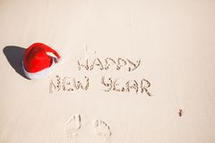 Happy New Year written in the sand and Santa Hat. On white sandy beach. See my other works in portfolio Royalty Free Stock Images