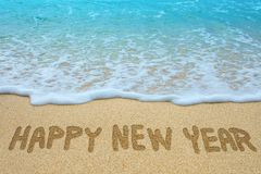 Happy new year written on sandy beach. With sea royalty free stock photo