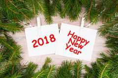 Happy New Year written on white sheets. Happy new year is written on white sheets with pendulous branches and garlands Royalty Free Stock Images