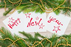 Happy New Year written on white sheets. Happy new year is written on white sheets with pendulous branches and garlands Stock Images
