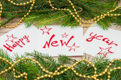 Happy New Year written on white sheets. Happy new year is written on white sheets with pendulous branches and garlands Stock Photography