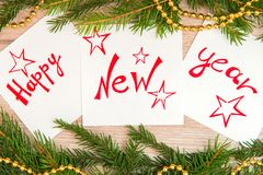 Happy New Year written on white sheets. Happy new year is written on white sheets with pendulous branches and garlands Royalty Free Stock Photography
