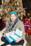 Happy new year, xmas, eve, party. Guy smile with gift boxes at Christmas tree. Winter holidays preparation, celebration. Man in hat, sweater hold wrapped Stock Photography
