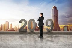 Happy New Year 2019. Young asian businessman standing with 2019 number on the rooftop. Happy New Year 2019 royalty free stock images