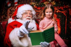 Happy new year. A happy young girl is sitting with Santa Claus at home. Merry Christmas and Happy New Year. Miracle time stock photography