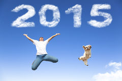 Happy new year 2015.young man and dog  jumping. Together with blue sky background Royalty Free Stock Photo