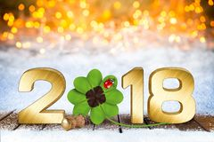 Happy new years eve silvester background. Happy new years eve silvester golden 2018 number with four-leaf clover and ladybug in front of bright bokeh background Stock Photos