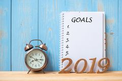 2019 Happy New years with Goals text on notebook, retro alarm clock and wooden number on table and copy space. Resolution, Mission and New Start Concept stock images