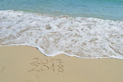 Happy New Years 2017 and 2018 handwritten on sand. With a wave coming to erase 2017. Turquoise mediterranean sea and with foam natural background royalty free stock photos