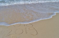 Happy New Years 2018 and 2019 handwritten on sand. With a wave coming to erase 2018. Turquoise mediterranean sea, with white foam and fine sand beach. Natural stock photography