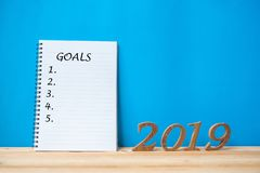 "2019 Happy New years with notebook "" Goals "" text and wooden number on table and copy space. stock image"