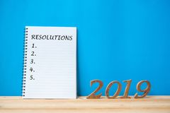 "2019 Happy New years with notebook ""Resolutions "" text and wooden number on table and copy space stock images"