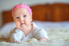 Happy newborn baby lies on a chair in a beautiful pink knitted crown royalty free stock photography