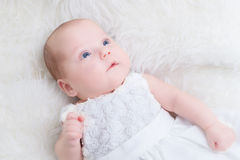 Happy newborn baby lying on white soft fur blanket. Royalty Free Stock Photography