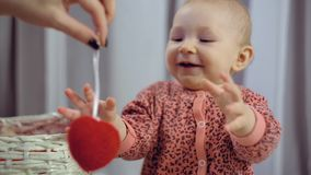 Happy newborn baby smiling and playing with heart stock video